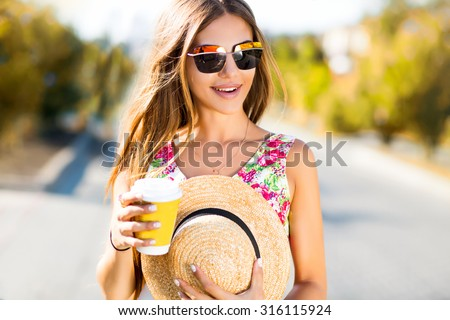 Laughing portrait of sensual woman drinking coffee on the city street,summer sale,travel concept,cute trendy glamour outfit,drinking hot latte,smiling enjoy weekends,travel with straw hat,cappuccino  - stock photo