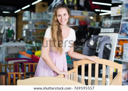 Laughing pregnant woman choosing cot for baby at infant shop