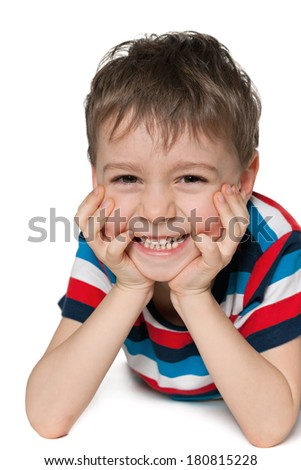 Laughing preschool boy is lying on the white background - stock photo