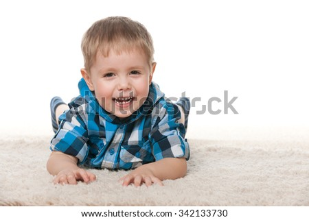 Laughing preschool boy is lying on the white carpet - stock photo