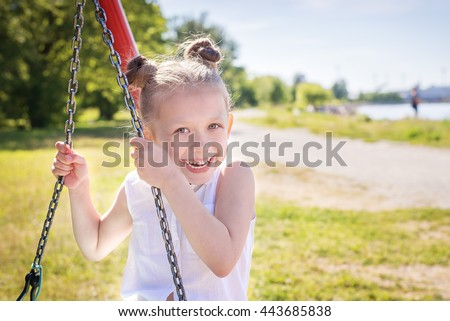 Laughing pretty girl on swing in summer beach park - stock photo