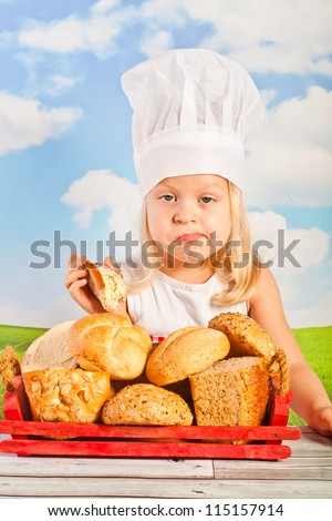 laughing pretty little girl in a cap with a basket chef bread, bread them, a slice of buttered chlebka heart-shaped cake - against a blue sky.