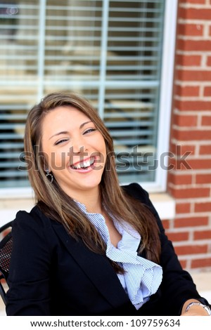 Laughing Professional Brunette Business Woman Sitting Down on a Lunch Break - stock photo