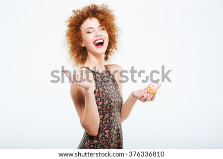 Laughing redhead woman eating cake isolated on a white background - stock photo