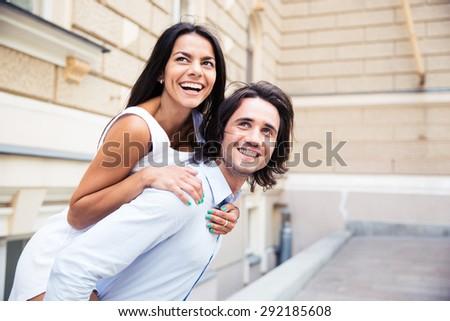 Laughing romantic couple having fun outdoors - stock photo