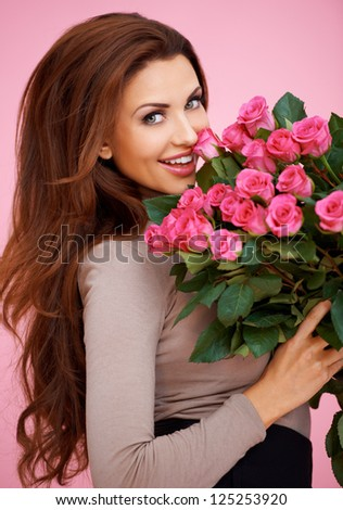 Laughing romantic sexy woman with long brunette hair holding a large bouquet of pink roses for her anniversary or Valentines - stock photo