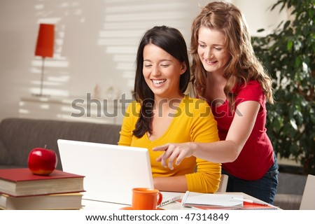 Laughing schoolgirls looking at laptop, blond girl pointing at screen. - stock photo