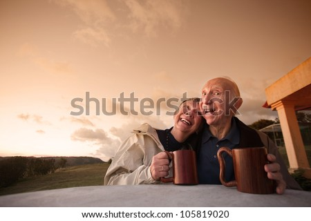 Laughing senior couple at table outside with coffee