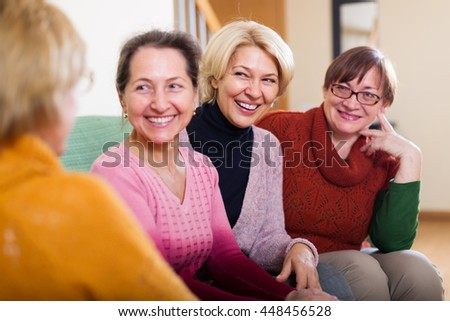 laughing senior friends chatting in living room at home