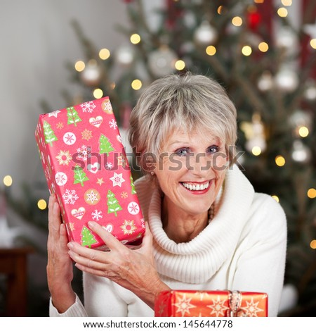 Laughing senior lady with a Christmas gift holding it up to her face in front of a tree with a sparkling bokeh of lights - stock photo