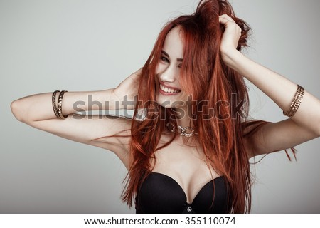 Laughing sexy busty young redhead woman in a black bikini isolated studio portrait - stock photo