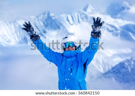 Laughing skier in helmet and blue winter outfit with his hands up, mountains in the background - stock photo