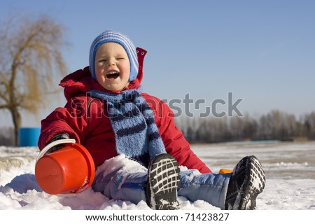 Laughing small child in the winter on snow - stock photo