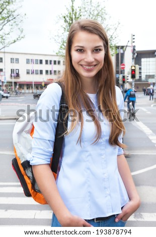 Laughing student with blond hair in the city - stock photo