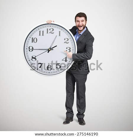 laughing successful businessman in formal wear pointing at clock dial and looking at camera over light grey background - stock photo