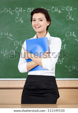 Laughing teacher at the blackboard hands a blue folder