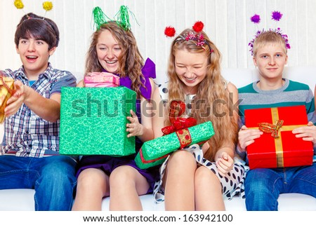 Laughing teen friends sit on the sofa with presents - stock photo