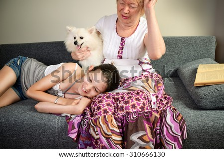 laughing teen girl and her grandmother with the dog. horizontal