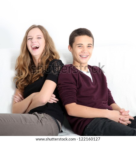 Laughing teenaged brother and sister sitting leaning on each other enjoying a good joke, square format with copyspace