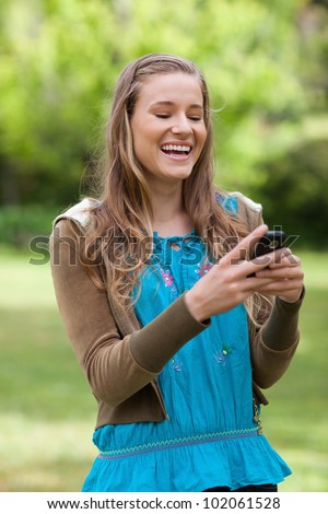 Laughing teenager standing in a park while receiving a text on her mobile phone