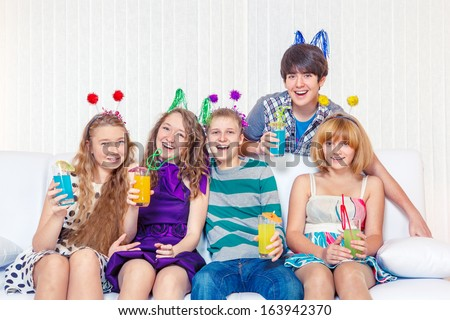 Laughing teenagers at the birthday party - stock photo