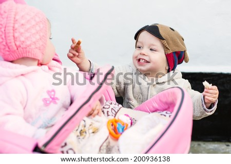 Laughing toddler baby boy feeding bread baby girl in a stroller - stock photo