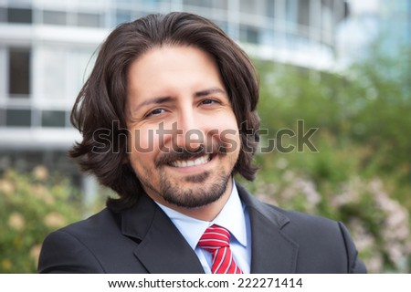 Laughing turkish businessman with suit in front of his office - stock photo