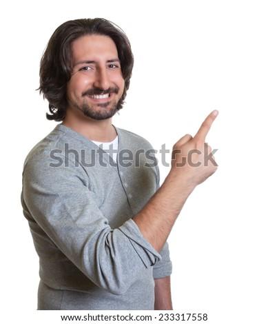 Laughing turkish guy pointing sideways - stock photo