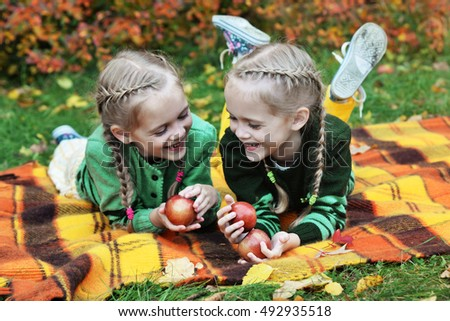 laughing twin sisters laying on plaid with apples. Colorful autumn park.