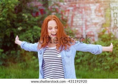 Laughing vivacious young woman enjoying herself twirling round in a lush spring garden with her arms outspread - stock photo
