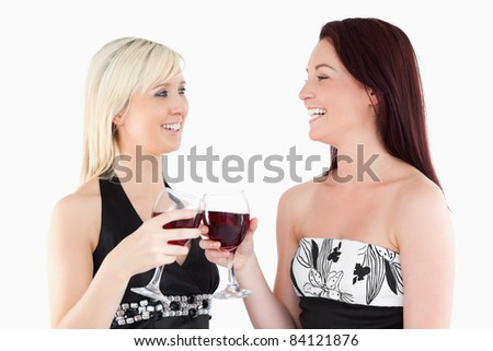 Laughing well-dressed women toasting with red wine in a studio