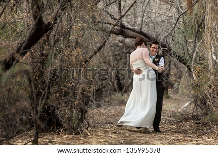 Laughing white Lesbian couple dancing in a forest - stock photo