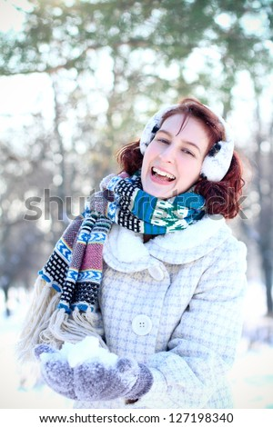 Laughing winter girl holding a snow in hands - stock photo