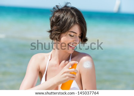Laughing woman applying suntan lotion to her shoulder from a spray bottle as she stands on the seashore overlooking the ocean - stock photo