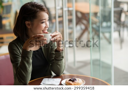 Laughing woman drinking tea and looking through the caf�© window - stock photo