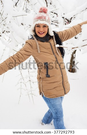 Laughing woman having fun in park with snow