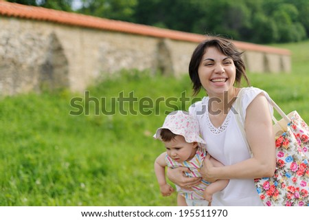 laughing woman holding her baby - stock photo
