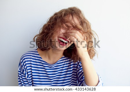 Laughing woman in marine shirt with curly hair over white wall. Toothy smile and red lips. - stock photo