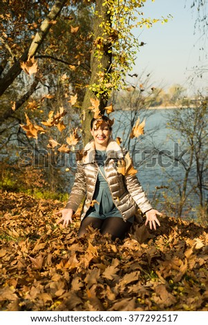 Laughing woman in park tossing autumn leaves
