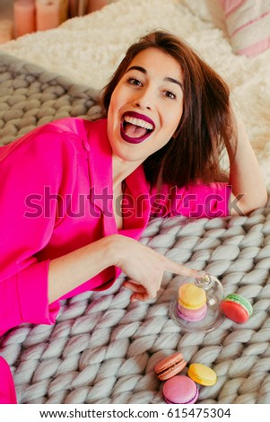Laughing woman in pink dress lies on bed with macaroons