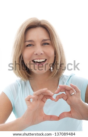 Laughing woman making a heart gesture with her fingers to show her love for something, isolated on white