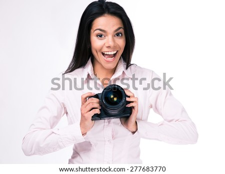 Laughing woman photographer with camera standing over gray background. Looking at camera
