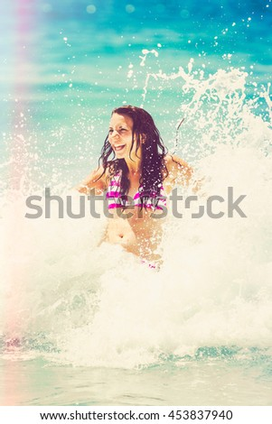 Laughing woman playing in the surf - stock photo