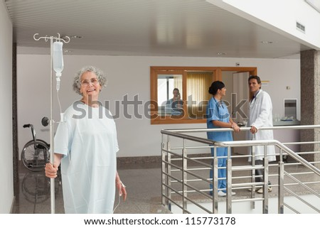 Laughing woman standing in the hallway holding a drip in her hands - stock photo