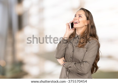 Laughing woman talking on the phone and looking up - stock photo