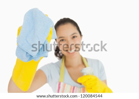 Laughing woman wiping with a blue rag wearing rubber gloves and apron - stock photo