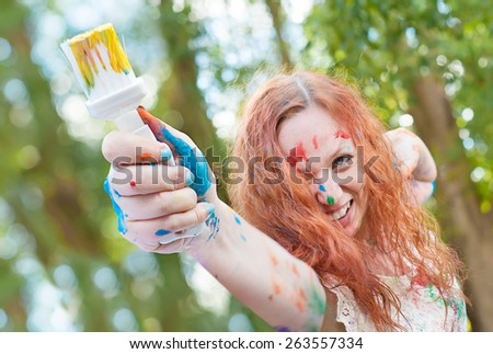 Laughing woman with the paintbrush is ready for creative battle - stock photo
