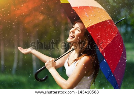 Laughing woman with umbrella checking for rain - stock photo