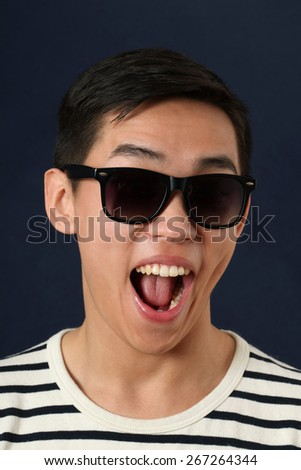 Laughing young Asian man in sunglasses - stock photo
