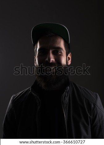 Laughing young bearded man with baseball cap looking at camera. Low key dark shadow portrait over black background.